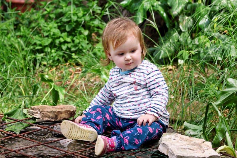 Schönes Babysitzen, lächelnd und werfen, Porträt auf Kleines nettes Mädchen ist im Garten spielerisch Kind spielt draußen im Park lizenzfreies stockbild