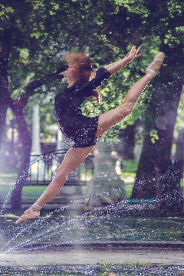 Schönes Ballerinamädchen in der zufälligen Kleidung, die auf einem unscharfen Hintergrund der Parkbäume auf Hintergrundfußnahaufn lizenzfreie stockbilder