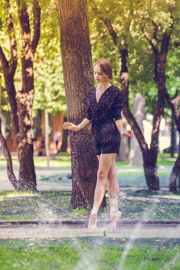 Schönes Ballerinamädchen in der zufälligen Kleidung, die auf einem unscharfen Hintergrund der Parkbäume auf Hintergrund aufwirft lizenzfreie stockbilder