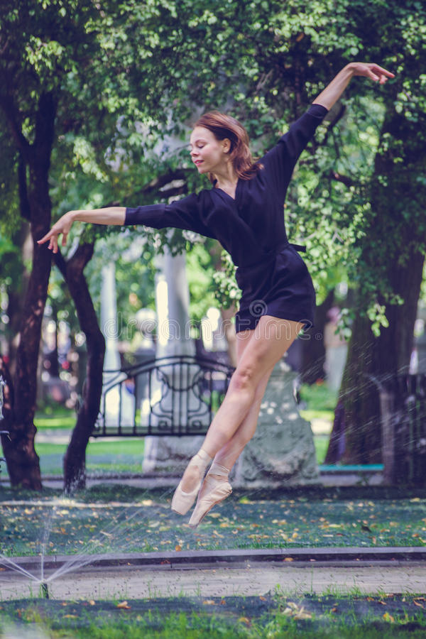 Schönes Ballerinamädchen in der zufälligen Kleidung, die auf einem unscharfen Hintergrund der Parkbäume auf Hintergrund aufwirft stockbilder