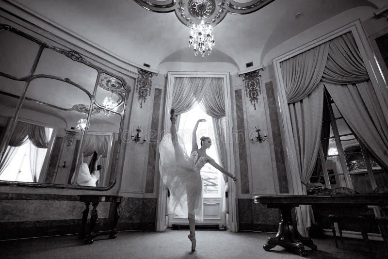 Schönes Ballerinatanzen in einer luxuriösen Halle mit einem Leuchter und Spiegeln lizenzfreies stockfoto