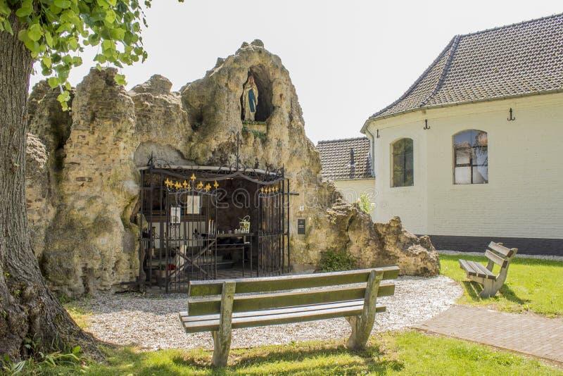 Schönes Bild einer Kapelle innerhalb eines Felsens mit einer Jungfrau Maria und Bänke stockbild