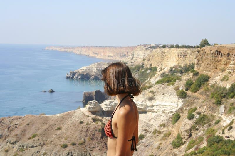 Schönes Bild von blauem Meer mit den Bergen nah und Stellung der jungen Frau lizenzfreie stockfotografie