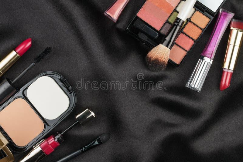 Schönes Bild von Kosmetik auf schwarzer Seide lizenzfreies stockfoto