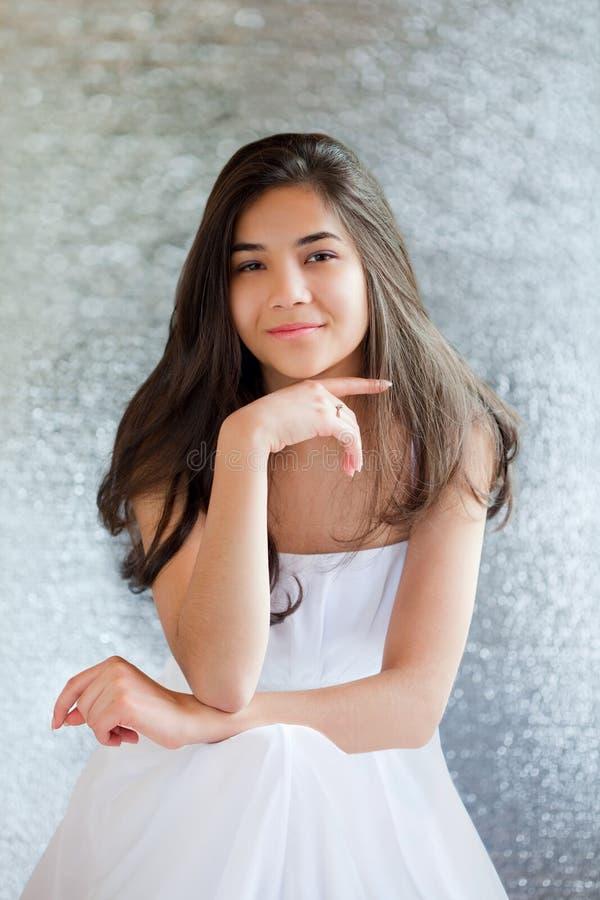 Schönes biracial jugendlich Mädchen im weißen Kleidersitzen, denkend lizenzfreie stockfotos