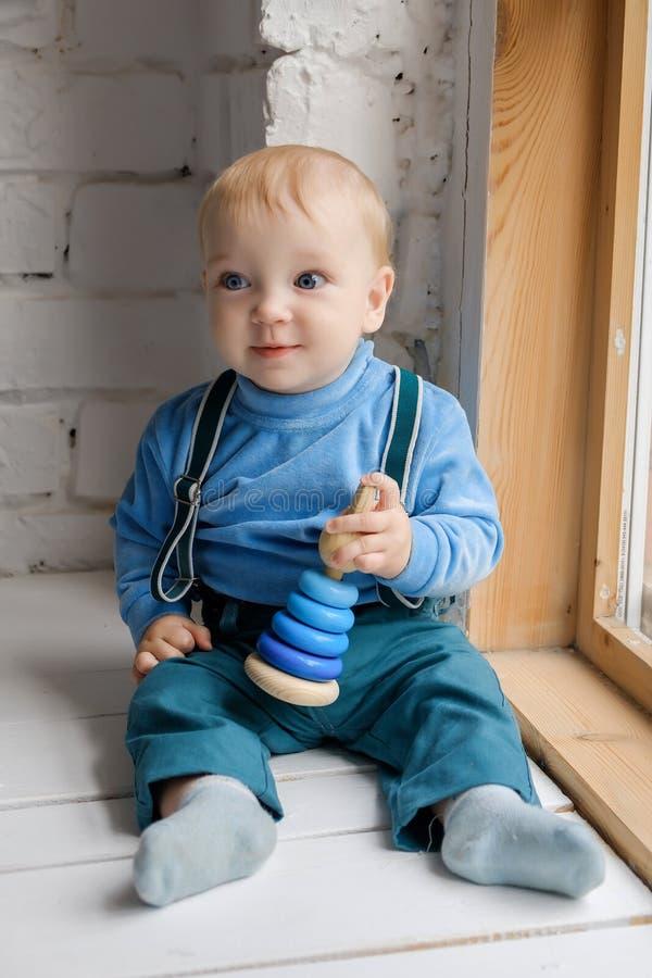 Schönes blauäugiges Baby, das auf dem Fensterbrett mit einer Spielzeugpyramide sitzt stockbilder
