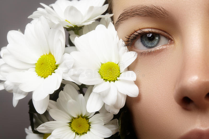 Schönes blaues weibliches Auge mit weißer Frühlingsblume Säubern Sie Haut, Mode naturel Make-up Gute Vision, Gesundheitswesen lizenzfreie stockfotografie