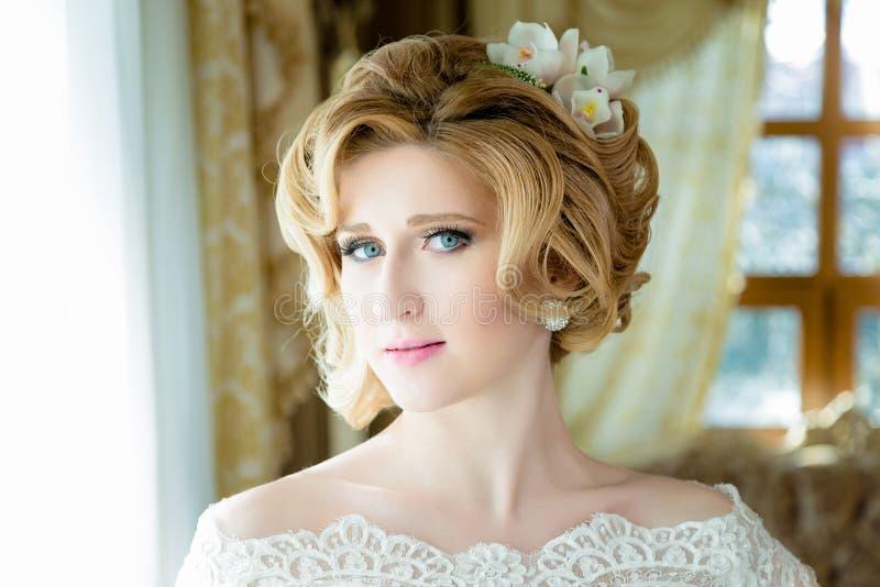 Schönes blondes Brautporträthochzeitsmake-up und -frisur stockfotografie