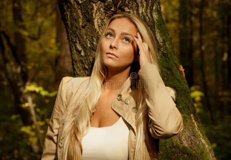 Schönes blondes Frauenporträt im Wald mit Suppengrün stockfoto