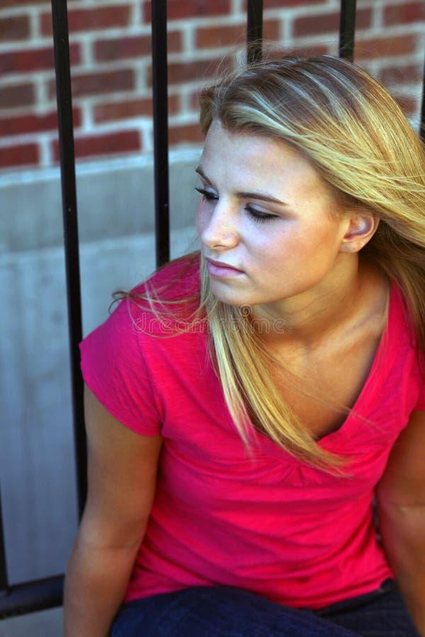 Schönes blondes jugendlich am Zaun lizenzfreie stockfotografie