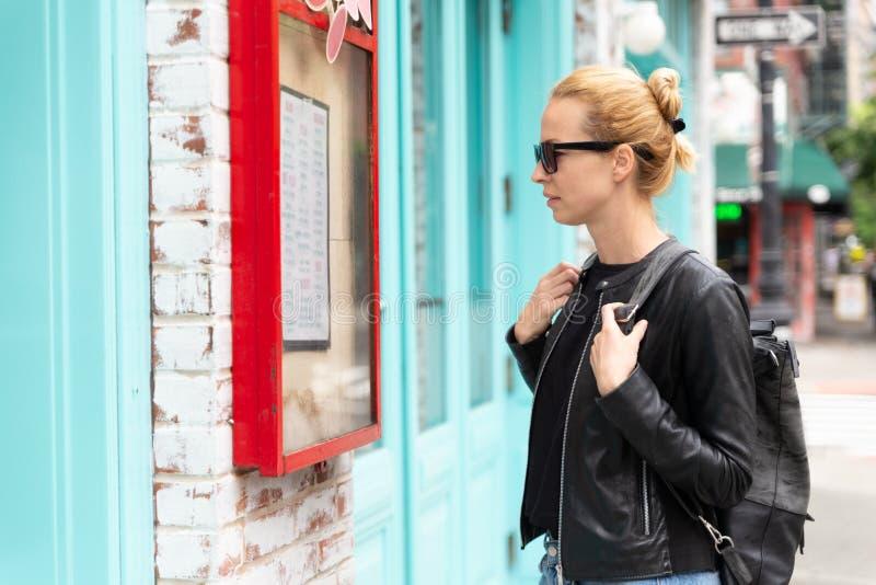 Schönes blondes junges weibliches touristisches Prüfungsrestaurantmenü draußen auf Städtereisewochenendausflug in New York City stockfotografie