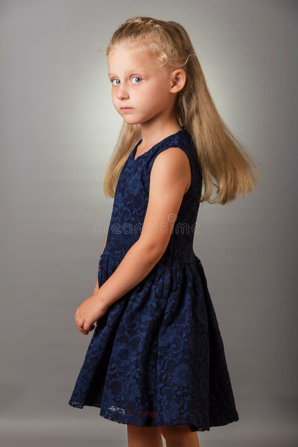 Schönes blondes kleines Mädchen in einem dunkelblauen Kleid auf grauem Hintergrund stockfoto