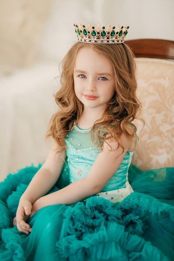 Schönes blondes kleines Mädchen im Kleid im Boudoir stockfotos