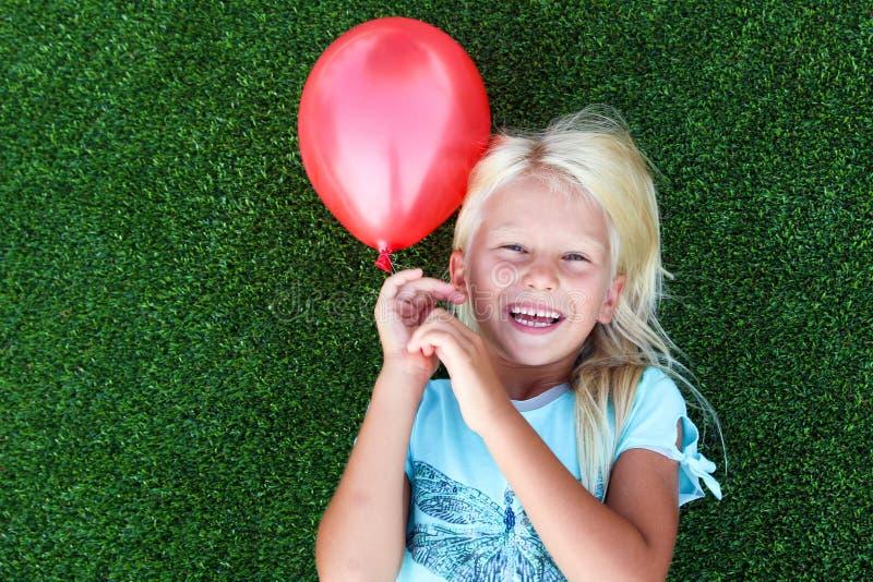 Schönes blondes lächelndes Mädchen, das auf dem Gras liegt und einen roten Ball hält stockfotografie