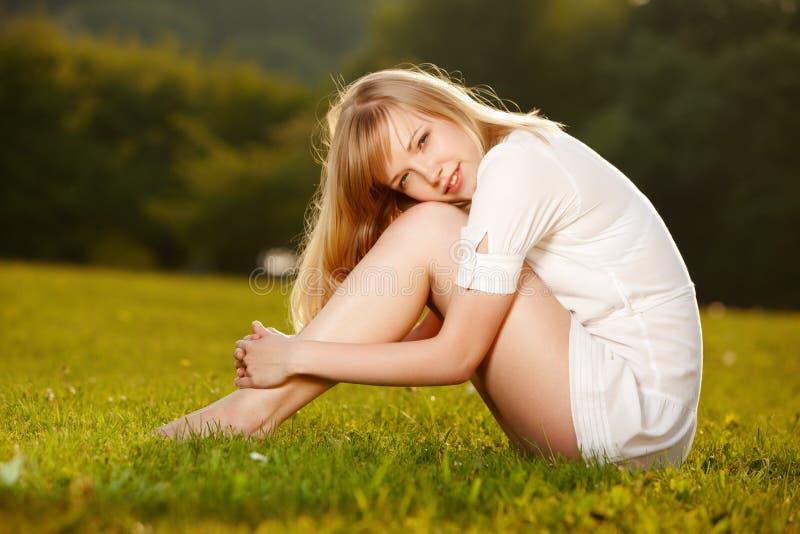 Schönes blondes Mädchen auf einem Gras lizenzfreies stockfoto