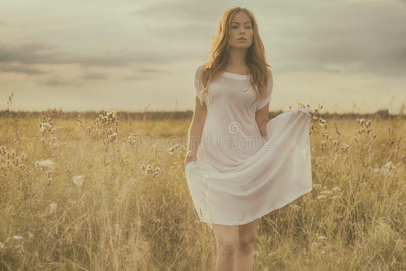 Schönes blondes Mädchen auf grünem Feld mit Blumen Landwirtschaftliche Szene stockfotografie