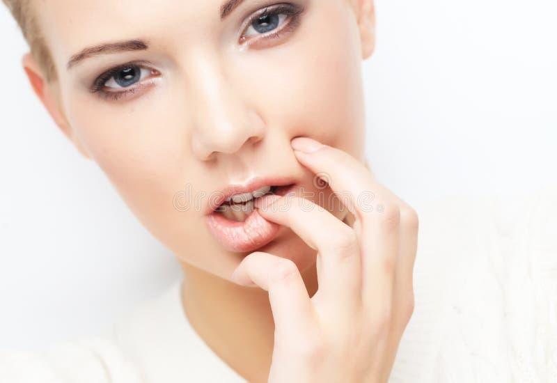 Schönes blondes Mädchen auf weißer Hintergrundnahaufnahme stockfotografie