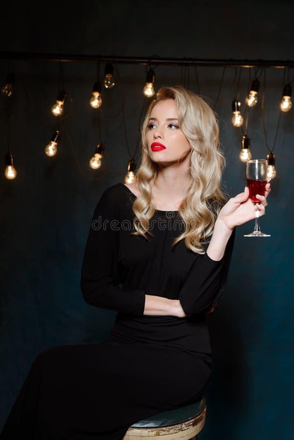 Schönes blondes Mädchen bei der Abendkleideraufstellung, Weinglas halten stockfotos