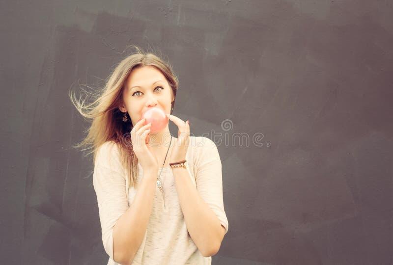 Schönes blondes Mädchen bläst eine rote Blase von Kaugummi auf outdoor stockfotos
