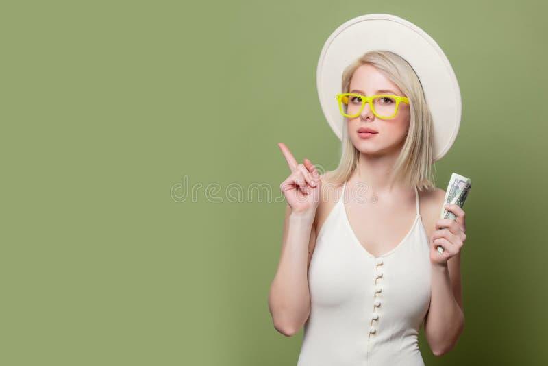 Schönes blondes Mädchen in Brille mit Geld stockfotografie