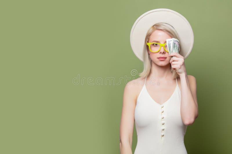 Schönes blondes Mädchen in Brille mit Geld lizenzfreie stockbilder