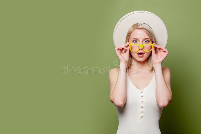 Schönes blondes Mädchen in Brille und weißer Hut stockbild
