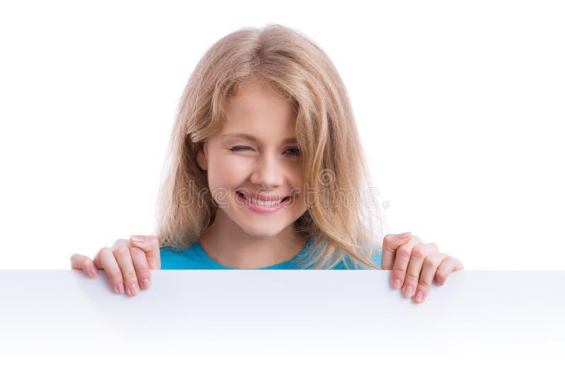 Schönes blondes Mädchen, das ein leeres weißes Brett hält stockfotos
