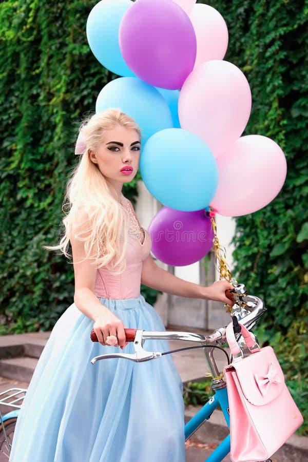 Schönes blondes Mädchen, das helle Ballone beim Radfahren hält stockfotografie