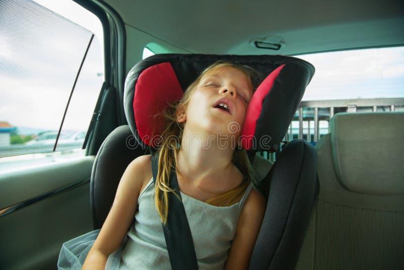 Schönes blondes Mädchen, das im Kindersitz im Auto schläft Kindertransportsicherheit lizenzfreie stockfotografie