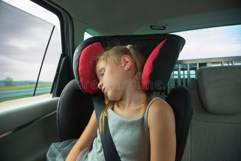 Schönes blondes Mädchen, das im Kindersitz im Auto schläft Kindertransportsicherheit lizenzfreie stockfotos