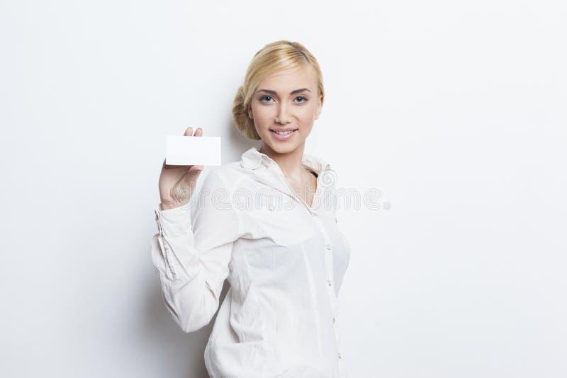 Schönes blondes Mädchen, das leere Visitenkarte hält stockfotografie