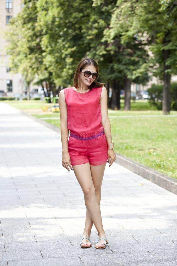 Schönes blondes Mädchen an der Straße Junge Frau in den roten kurzen Hosen und in einer Bluse stockfoto