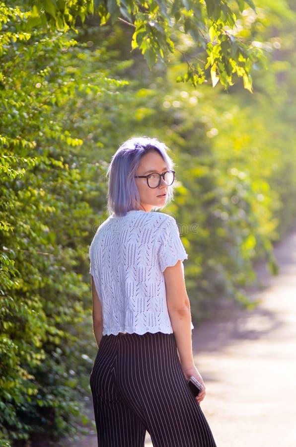 Schönes blondes Mädchen an der Straße Stilvoller Blick Blau-haariges Hippie-Mädchen in den Gläsern, die vor Kamera im Park aufwer stockfotos
