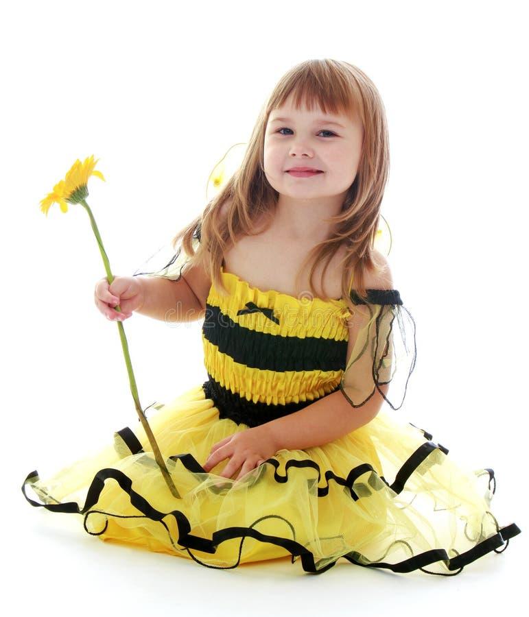 Schönes blondes Mädchen in einem gelben gestreiften Kleid lizenzfreie stockbilder