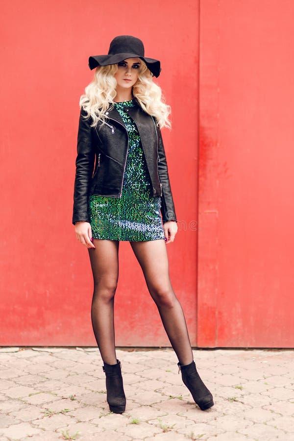 Schönes blondes Mädchen in einem glänzenden Kleid und in einer Lederjacke auf dem Hintergrund einer roten Wand lizenzfreies stockfoto