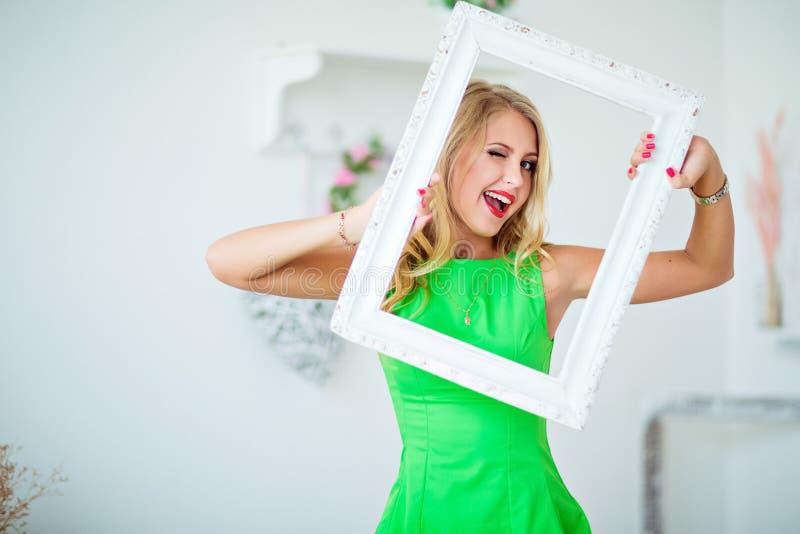 Schönes blondes Mädchen in einem grünen Kleid, das Rahmen und Winks hält lizenzfreie stockbilder