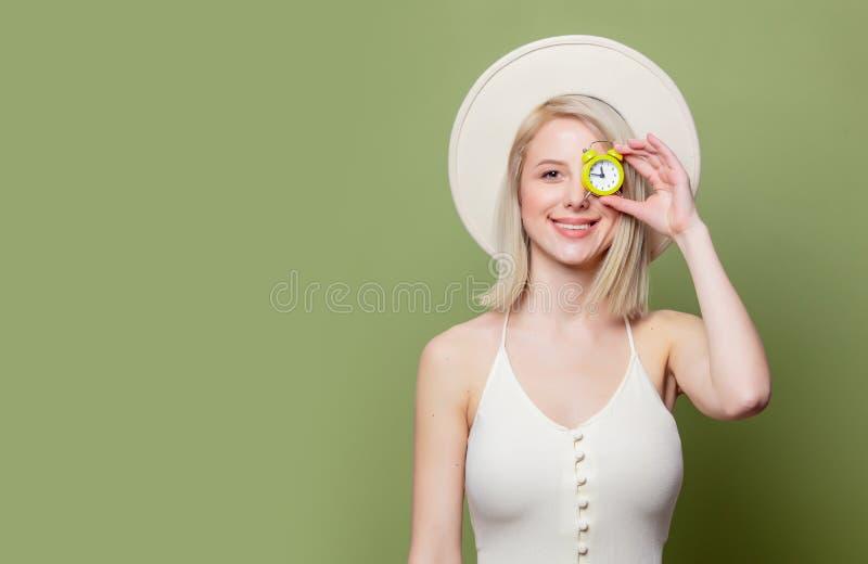 Schönes blondes Mädchen in einem weißen Hut und Kleid mit kleinem Wecker lizenzfreie stockbilder