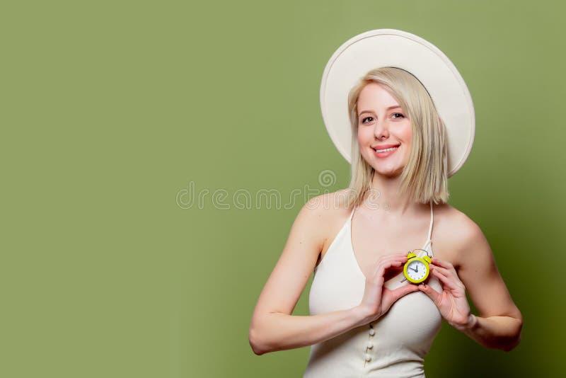 Schönes blondes Mädchen in einem weißen Hut und Kleid mit kleinem Wecker stockfotos