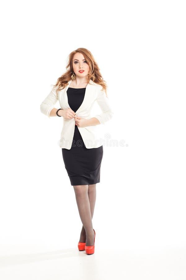 Schönes blondes Mädchen in einer schwarzen Kleiderweißjacke und roten Schuhen des hohen Absatzes auf dem Hintergrundstudio stockfotos