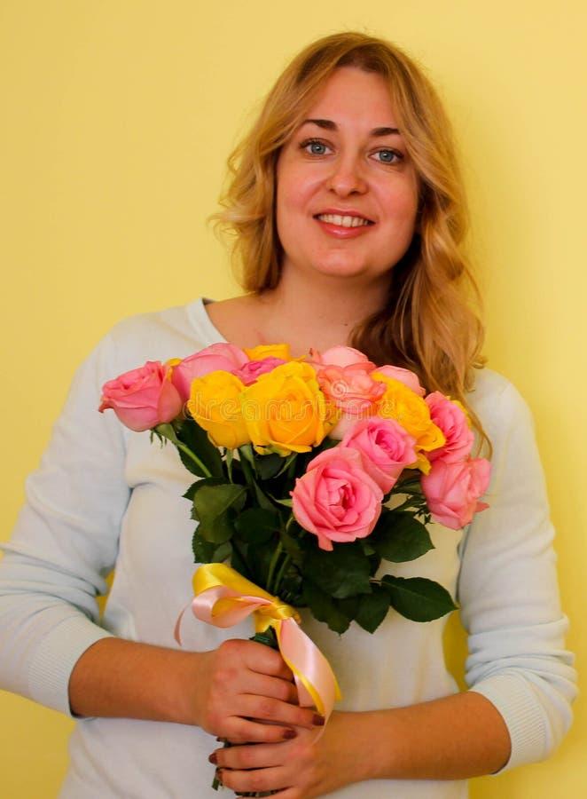 Schönes blondes Mädchen im blauen Kleiderholdingblumenstrauß von gelben und rosa Rosen auf einem hellgelben Hintergrund stockbilder