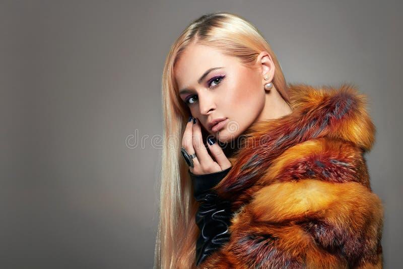 Schönes blondes Mädchen im bunten Pelz stockbilder
