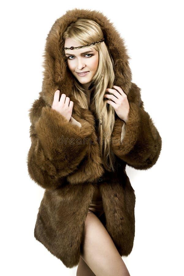 Schönes blondes Mädchen im Pelz mit Haube stockfotografie