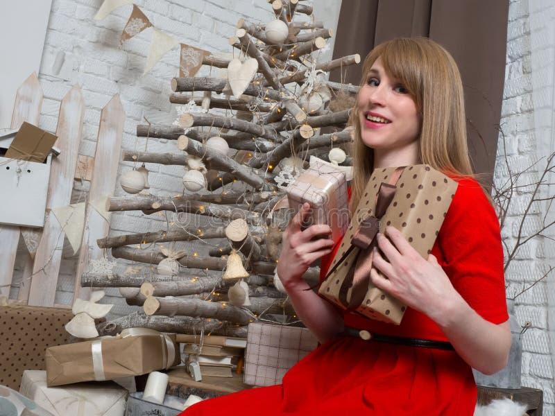 Schönes blondes Mädchen im roten Kleid und in den Geschenken des neuen Jahres Stimmung und Innenraum des neuen Jahres stockfotografie