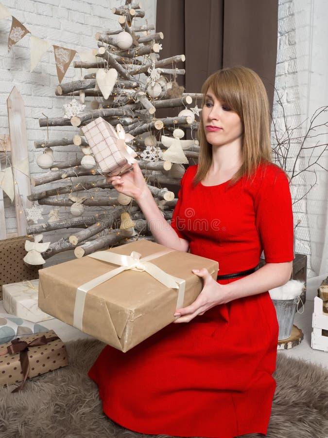 Schönes blondes Mädchen im roten Kleid und in den Geschenken des neuen Jahres Stimmung und Innenraum des neuen Jahres stockfotos