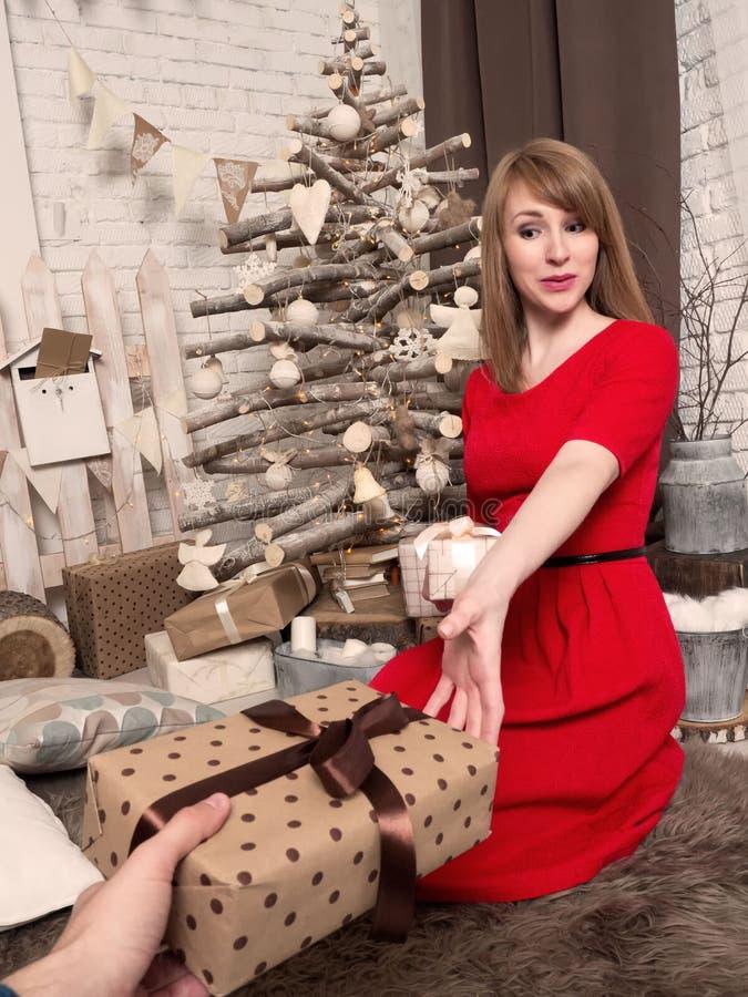 Schönes blondes Mädchen im roten Kleid und in den Geschenken des neuen Jahres Stimmung und Innenraum des neuen Jahres stockbilder
