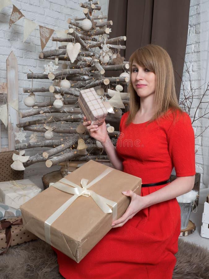 Schönes blondes Mädchen im roten Kleid und in den Geschenken des neuen Jahres Stimmung und Innenraum des neuen Jahres stockbild