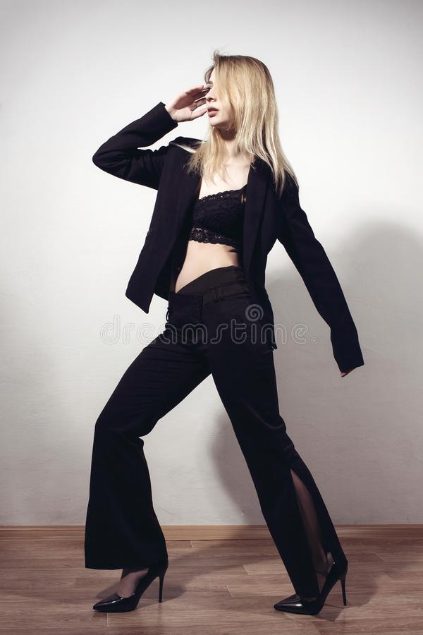Schönes blondes Mädchen im stilvollen Anzug tritt nahe der Wand lizenzfreie stockbilder