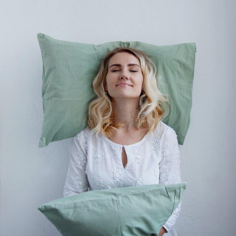 Schönes blondes Mädchen lehnte ihren Kopf auf dem Kissen Sie ist bereit zu schlafen oben stehend Kissen ist sehr bequem lizenzfreie stockfotografie