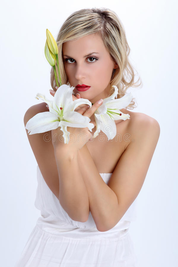 Schönes blondes Mädchen mit Blume der weißen Lilie auf einem Weiß lizenzfreies stockfoto