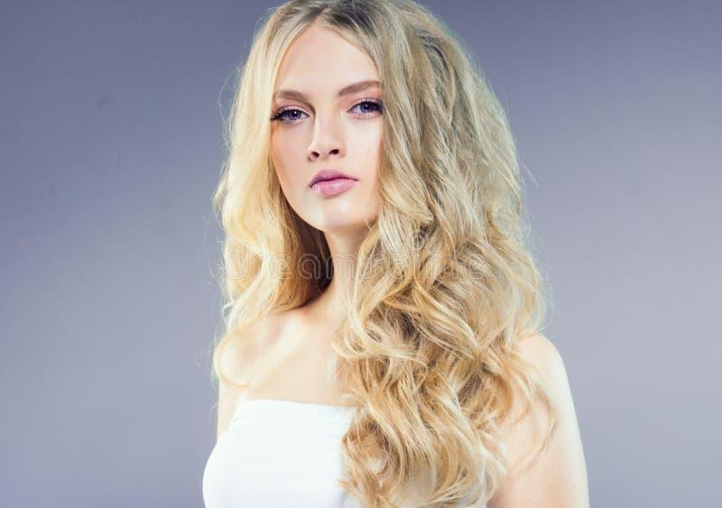 Schönes blondes Mädchen mit dem langen gelockten Haar über purpurrotem backgroun lizenzfreie stockfotos